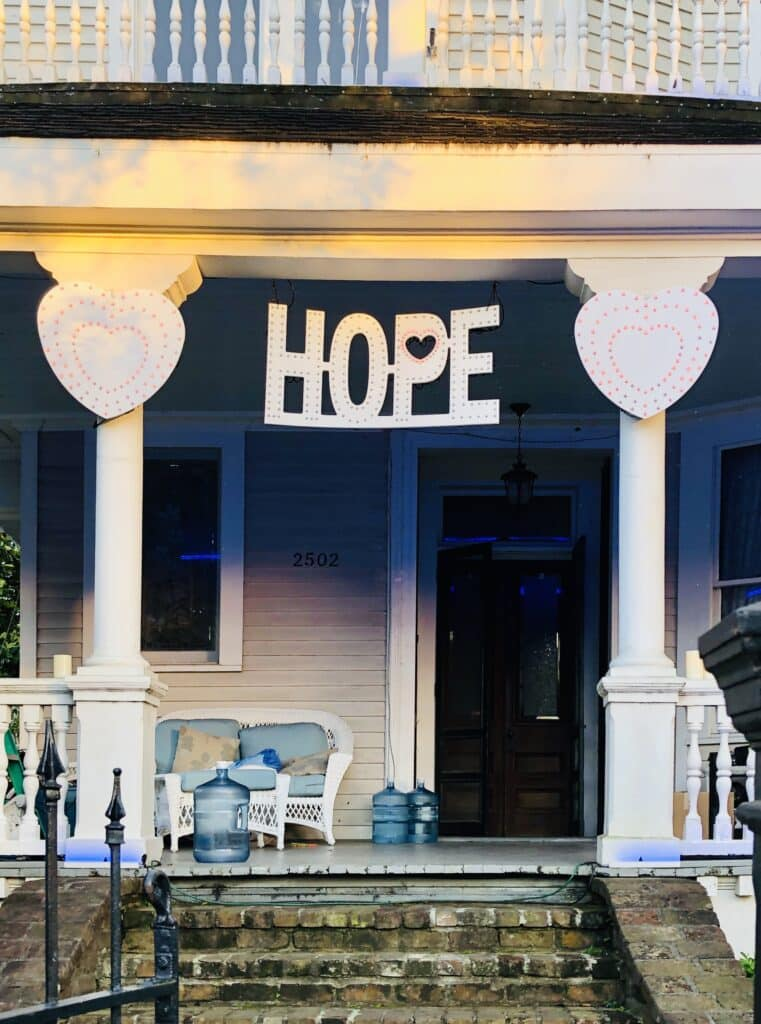 """The front porch of a house in New orleans with a hand-made sign that reads, """"HOPE."""""""